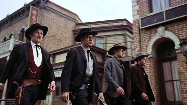 Doc Holliday, Wyatt, Virgil und Morgan Earp (gespielt von Kirk Douglas, Burt Lancaster, John Hudson und DeForest Kelley) marschieren bewaffnet an Häusern vorbei durch Tombstone