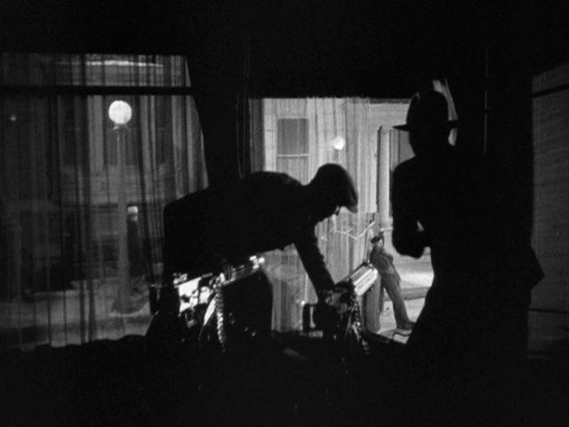 zwei Männer stehen im Dunkeln an zwei Maschinengewehren, die aus dem Fenster einer Wohnung auf die Straße gerichtet sind