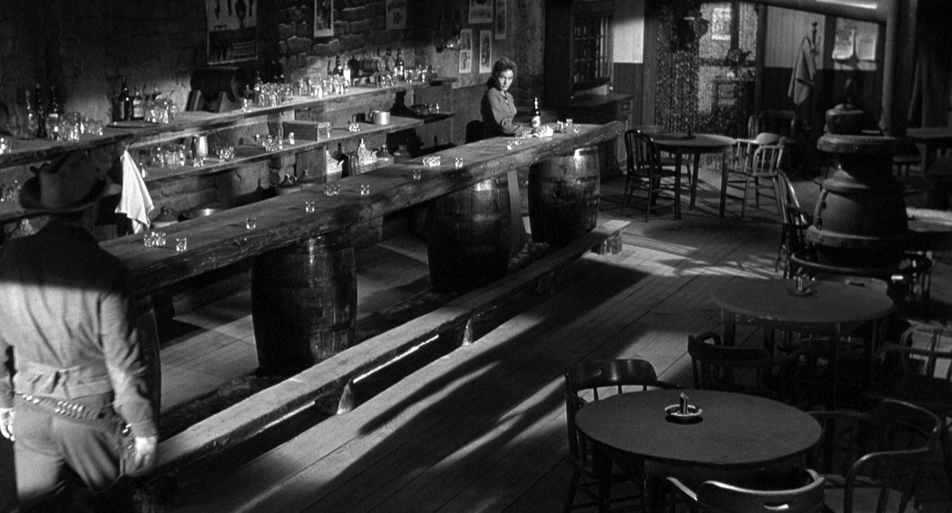 Expressionistische Schwarz-Weiß-Szene, in der ein Cowboy einen bis auf die Barkeeperin leeren Saloon betritt; man sieht sein Gesicht nicht, sie blickt von der anderen Seite des Raumes zu ihm.