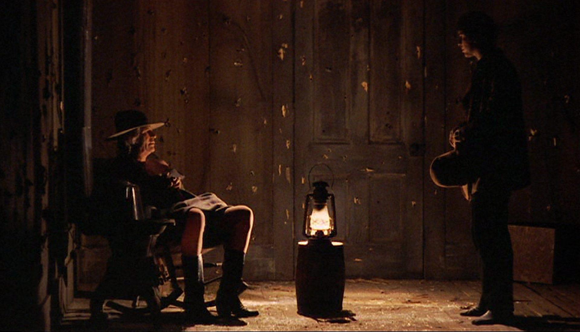 Blick in den düsteren Raum einer Holzhütte, in dem sich der Sheriff und ein junger Bandit gegenüberstehen.