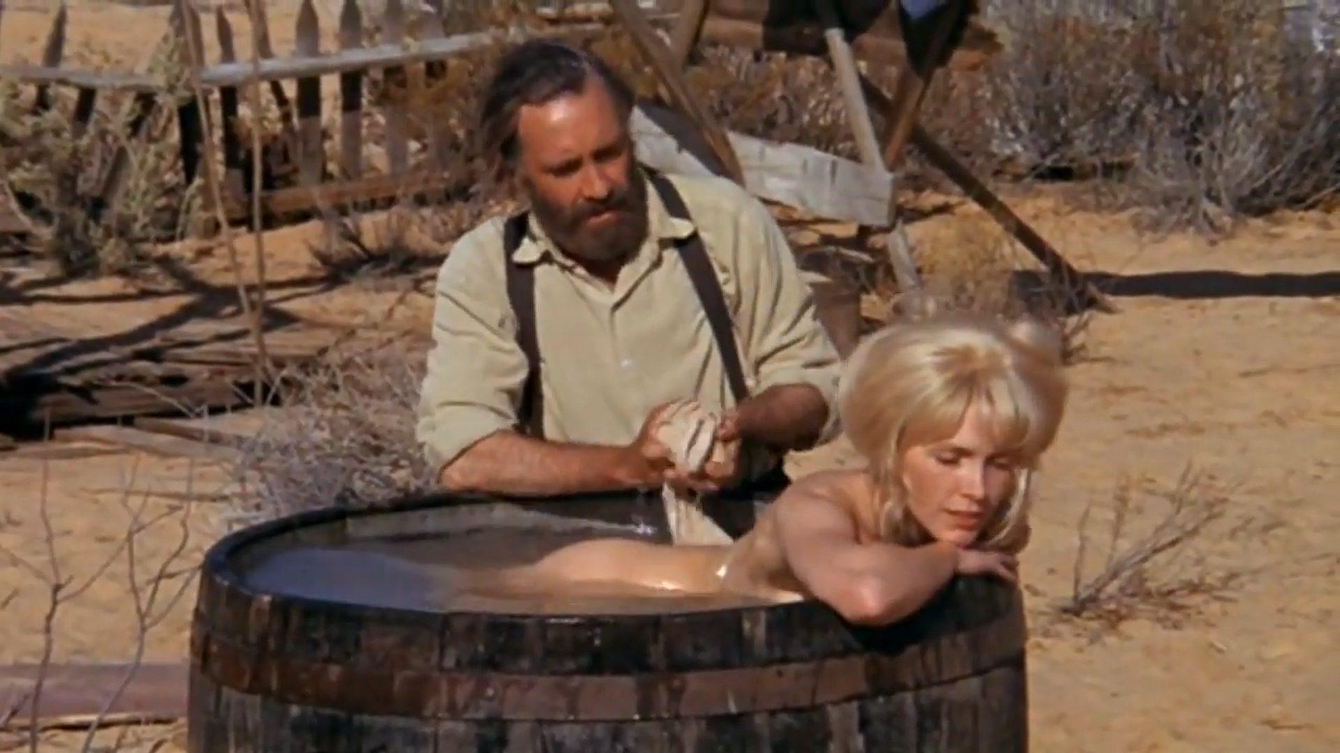 Cable Hogue, gespielt von Jason Robards, badet seine Freundin Hildy, gespielt von Stella Stevens, in einem großen Holzfass.