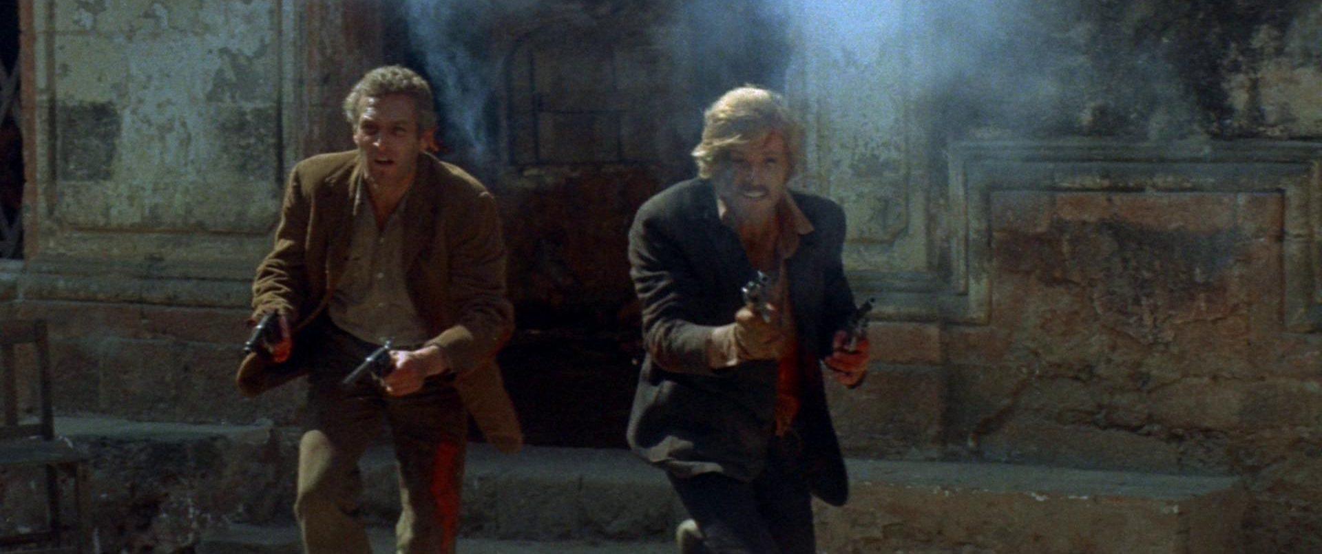 Paul Newman und Robert Redford als Butch Cassidy und Sundance Kid mit gezückten Revolvern inmitten einer Schießerei.