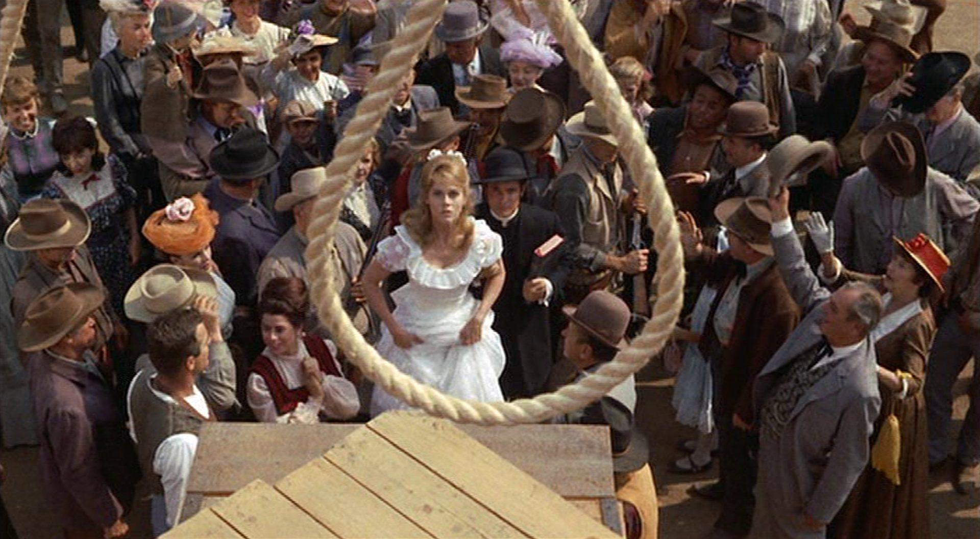 Blick durch die Galgenschlinge auf Cat Ballou in weißem Kleid inmitten eines Lynchpublikums.