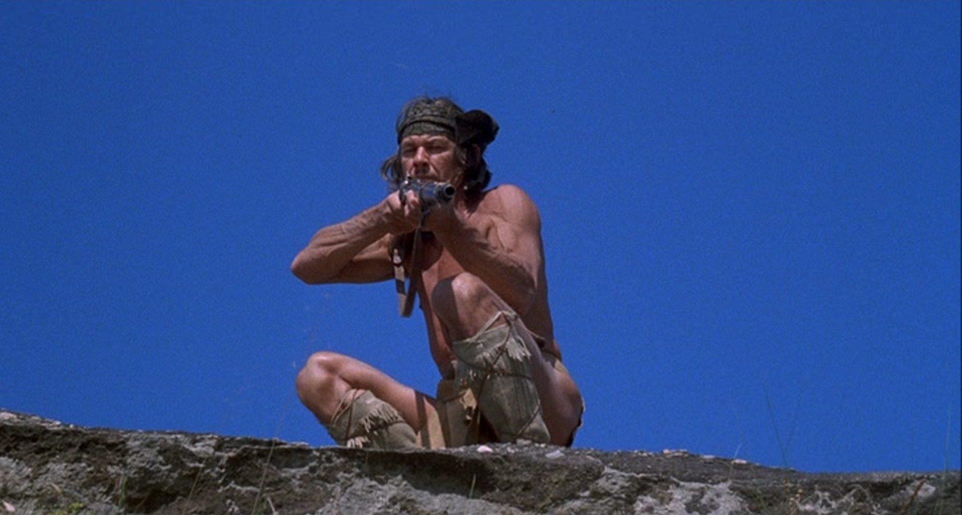 Charles Bronson als Chato vor blauem Himmel in kämpferischer Pose und mit Gewehr im Anschlag.