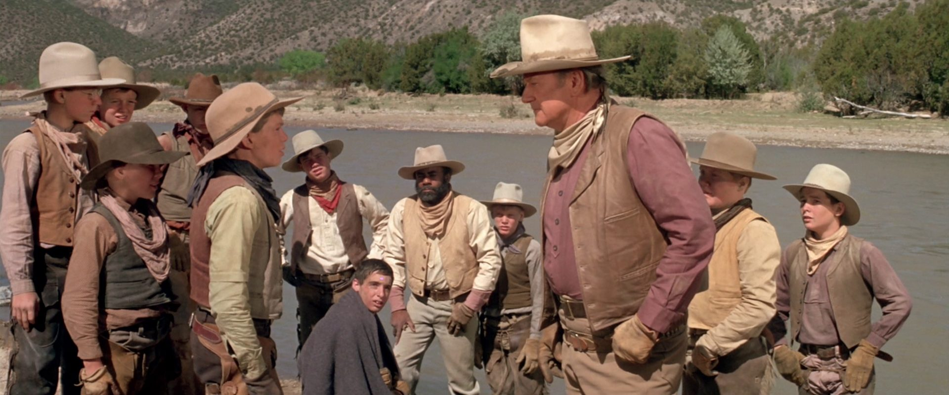 John Wayne als Viehbaron Wil Anderson vor großer Gruppe am Flussufer im Gespräch mit einem der Jungen, die er engagiert hat.
