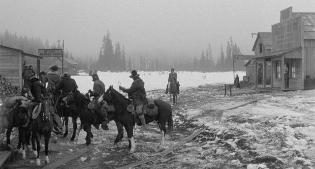 Blick in die von Scheematsch überzogene Straße eines winzigen Ortes; im Vordergrund warten einige Reiter zu Pferd, im Hintergrund deutet sich eine endlose Wildnis an.