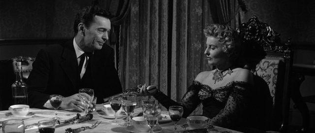 Griff Bonnell und Jessica Drummond sitzen sich am Tisch gegenüber, sie begutachtet seinen Revolver.