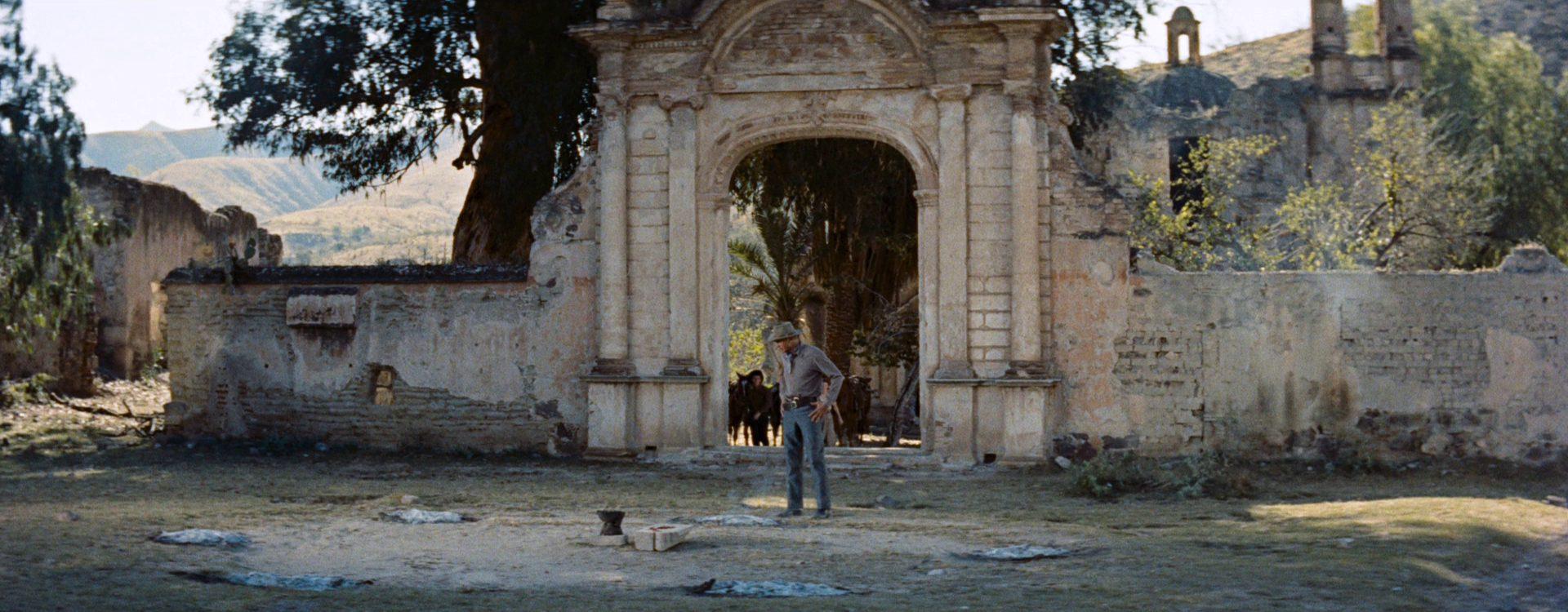 Hooker, gespielt von Gary Cooper, steht bei schönem Wetter vor der Mauer einer mexikanischen Ruine und blickt zu Boden.