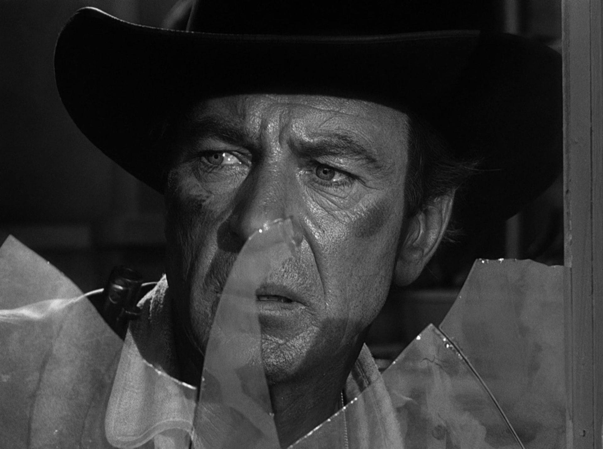 Nahaufnahme von Gary Cooper als Marshal Will Kane mit erschrocken-skeptischem Gesicht hinter einer zersplitterten Fensterscheibe.
