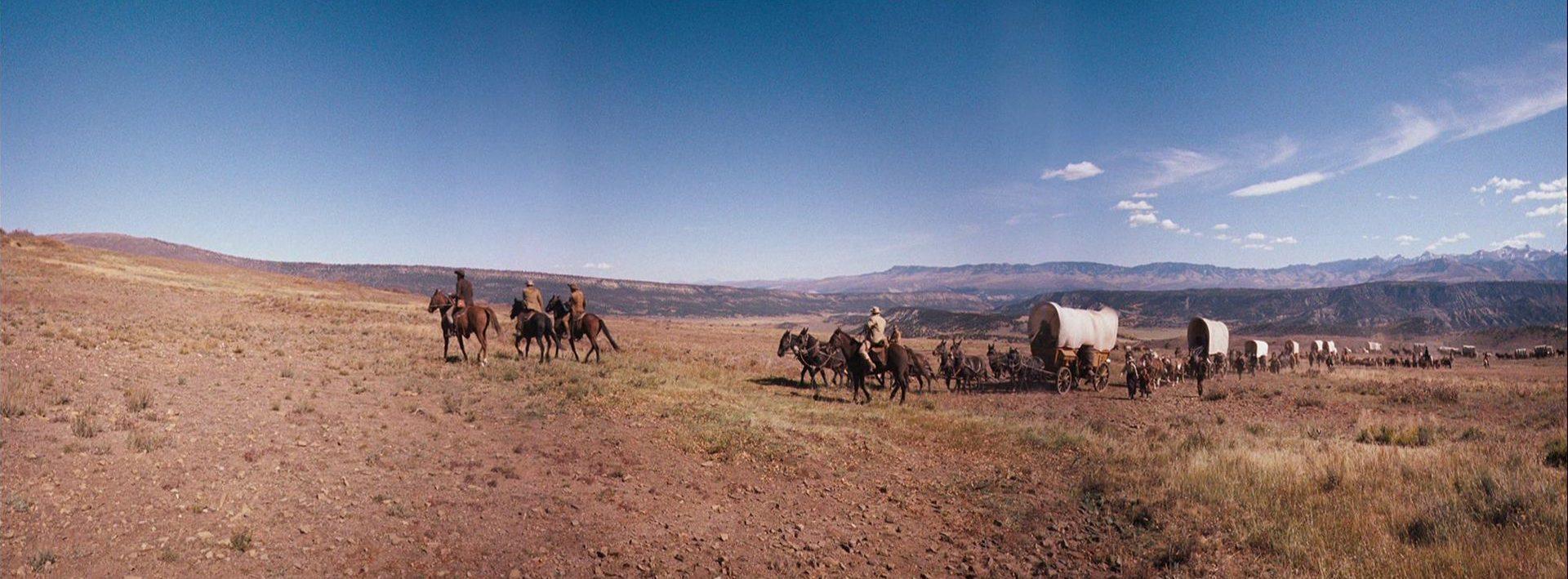 Ein Siedlertreck mit seinen Planwagen unterwegs durch die Prärie vor strahlend blauem Himmel.