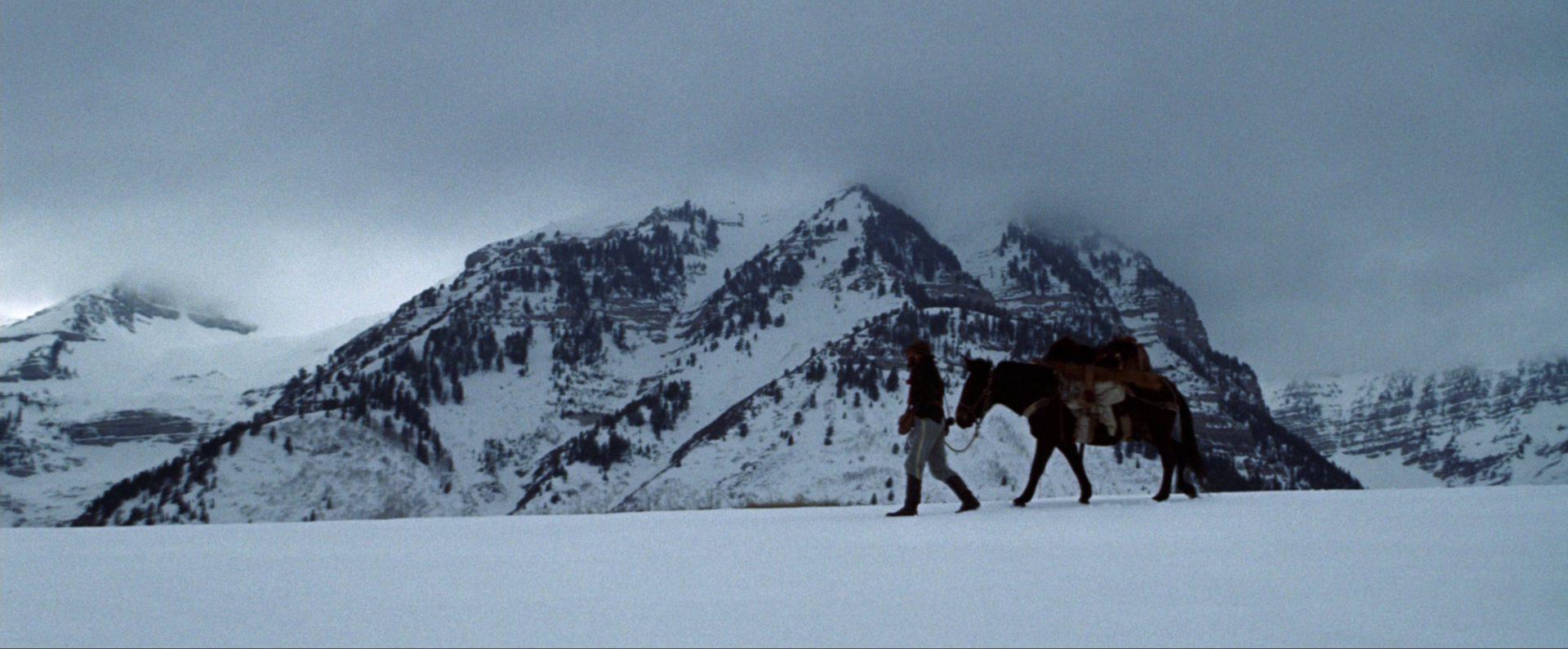 Robert Redford stapft als Jeremiah Johnson mit Pferd im an der Leine durch eine eisige Landschaft, im Hintergrund verschneites Gebirge.