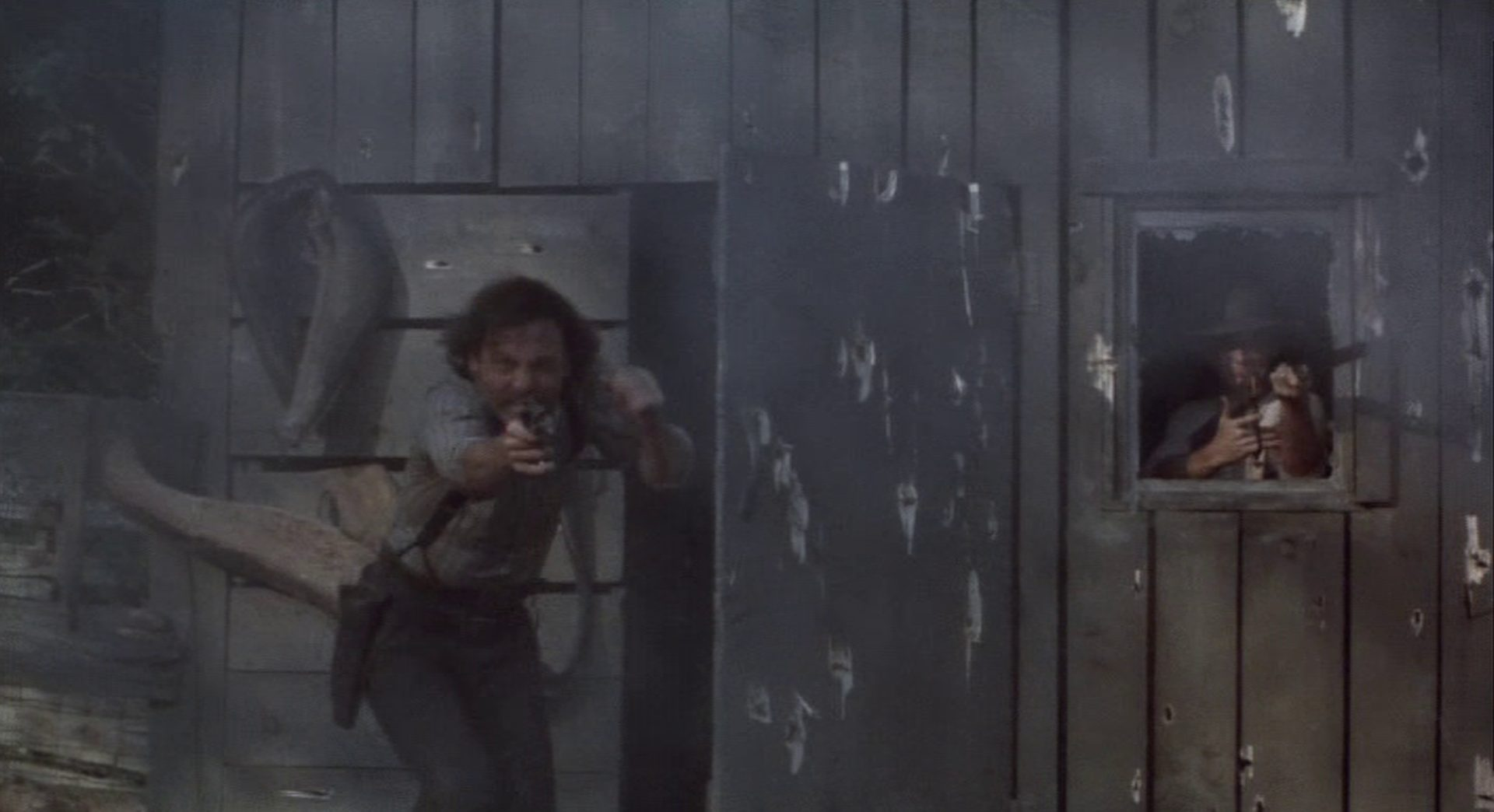 Zwei Gangster im Feuergefecht in einer von Kugeln durchlöcherten Holzhütte.