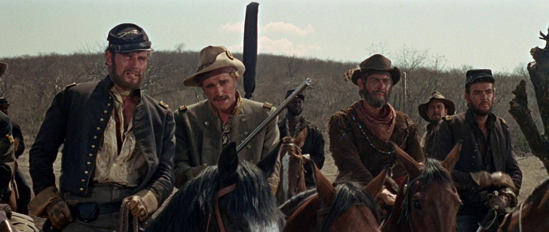 Nahaufnahme von Charlton Heston als Major Dundee zu Pferd in Begleitung seiner Mitstreiter (unter anderen Richard Harris als Konföderiertenoffizier und James Coburn als Scout).