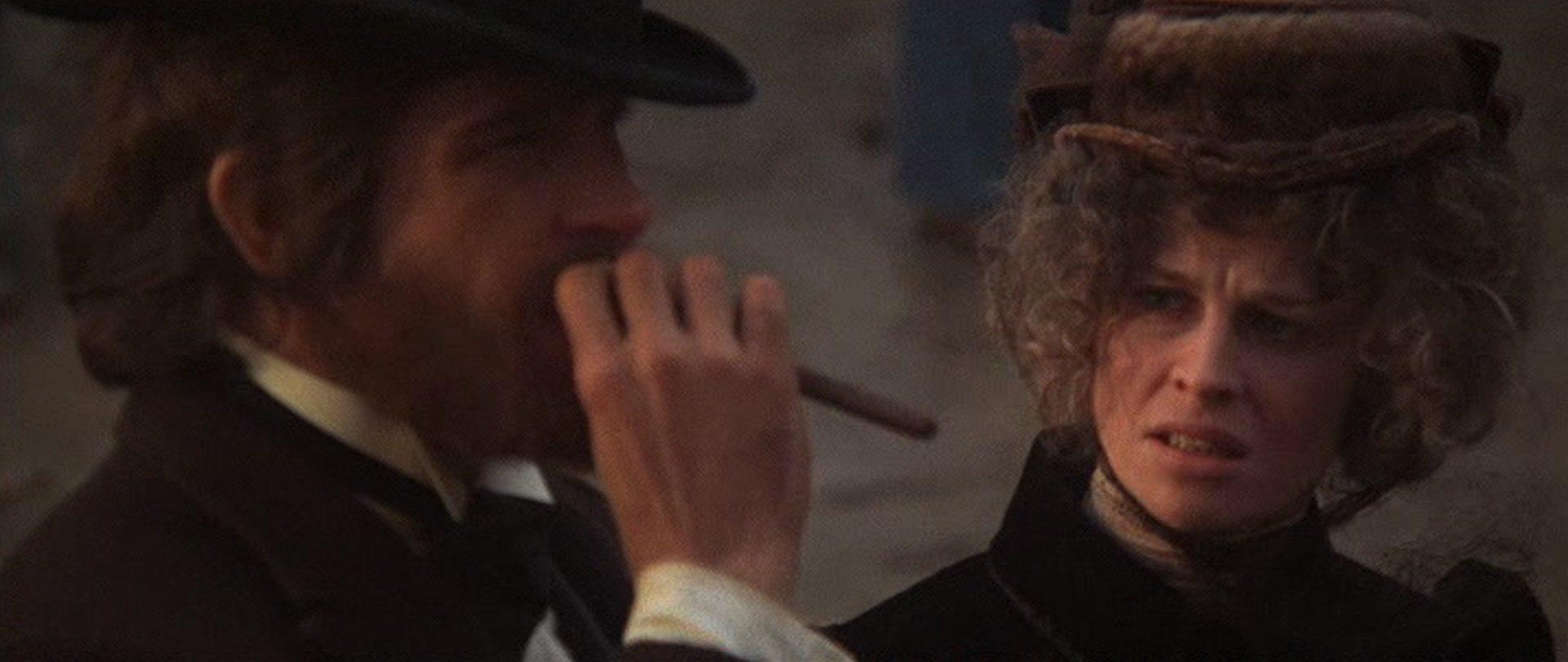 Nahaufnahme von Warren Beatty als John McCabe mit langer Zigarre und Julie Christie als Constance Miller, die ihn kritisch anblickt.