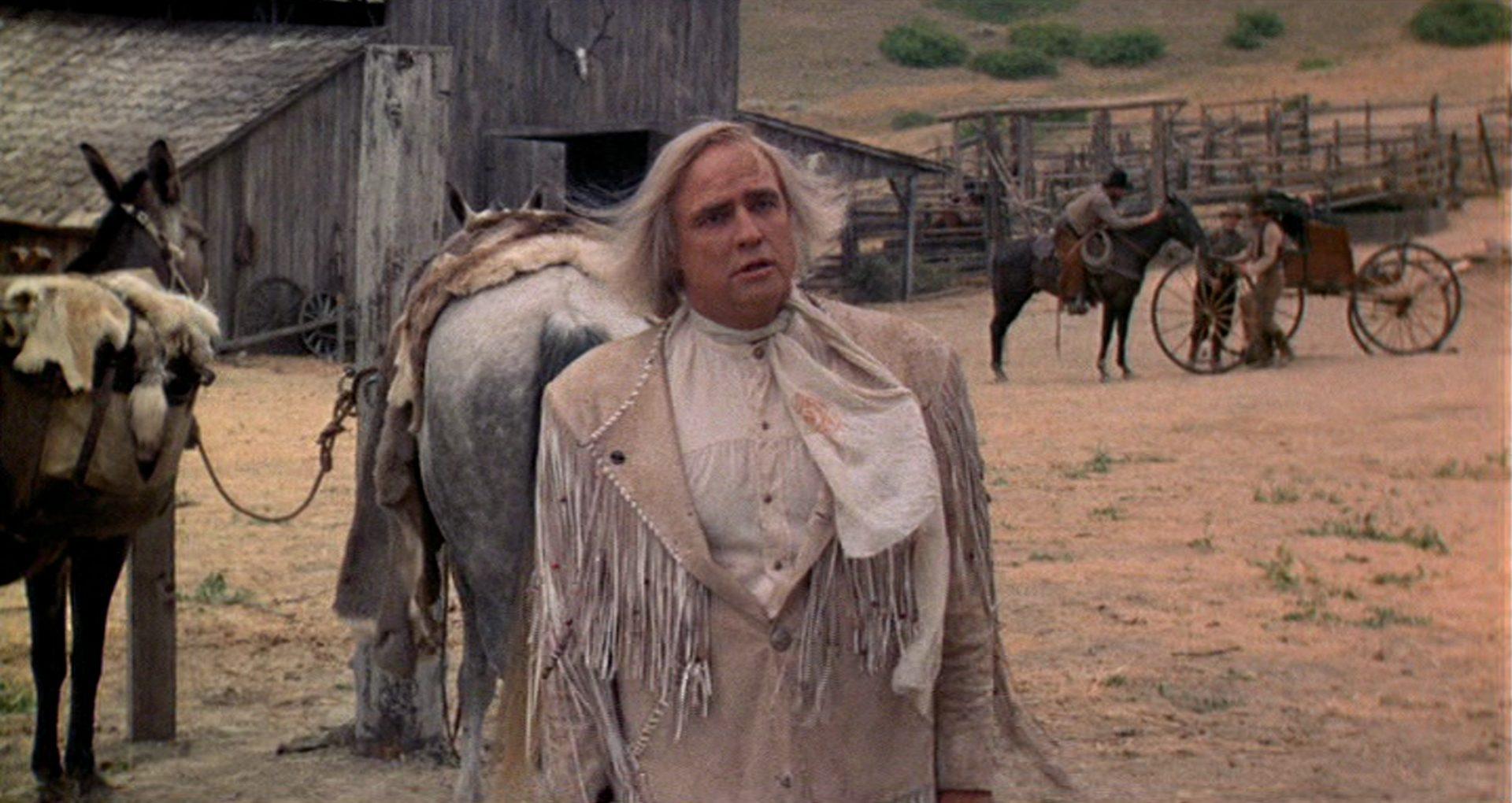 Marlon Brando als exzentrischer Killer vor dem Hintergrund eines Ranchgebäudes.