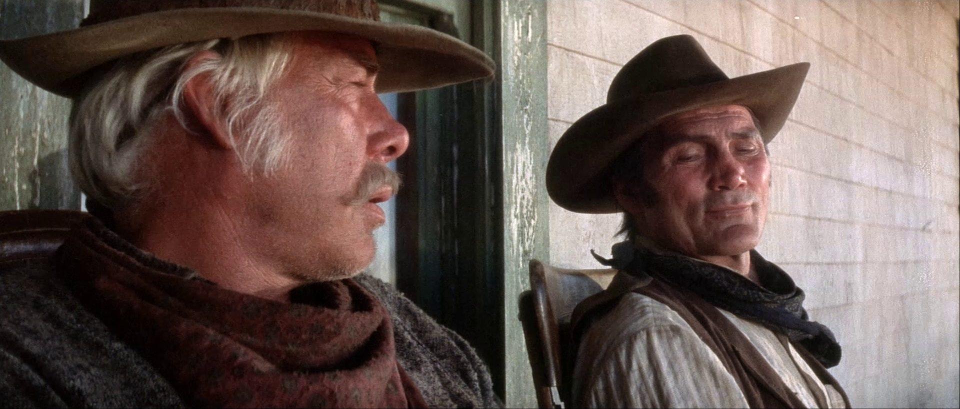 Nahaufnahme von Lee Marvin als Monte Walsh und Jack Palance als Chet Rollins, die in Stühlen auf einer Veranda sitzen.