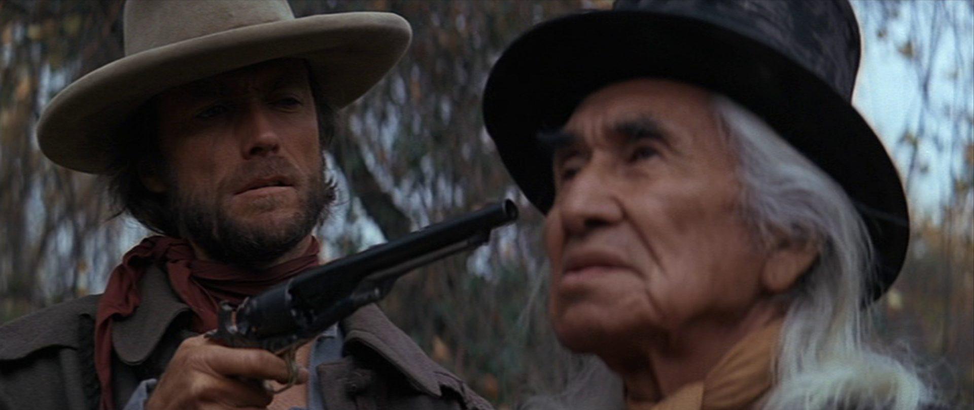 Nahaufnahme von Chief Dan George als Lone Watie, der von Clint Eastwood als Josey Wales mit einem Revolver bedroht wird.