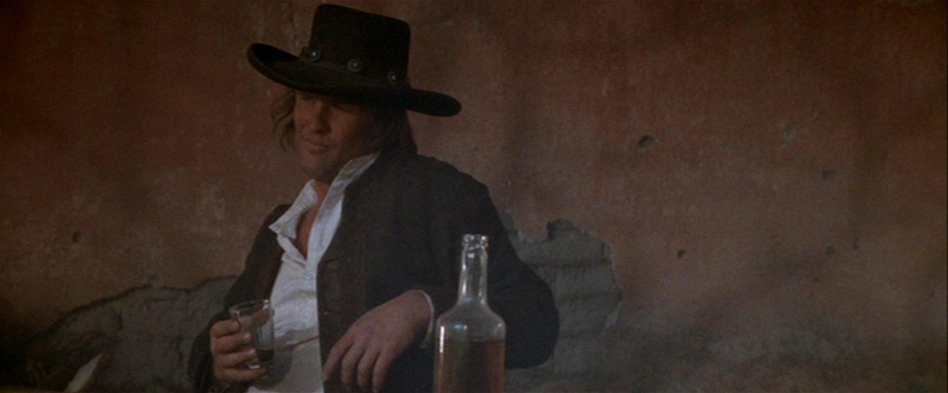 Kris Kristofferson als Billy the Kid, der lässig mit einem Drink in der Hand vor einer maroden Wand sitzt.
