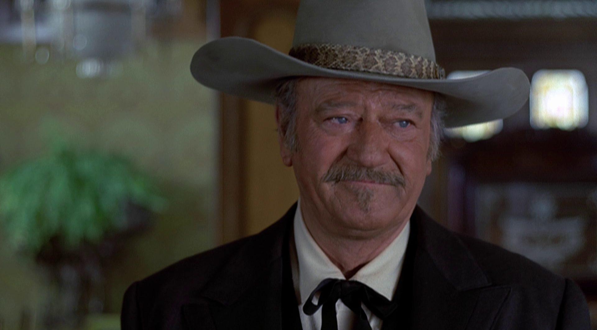Nahaufnahme von John Wayne als J.B. Book mit bedenklichem Gesicht und großem Hut.
