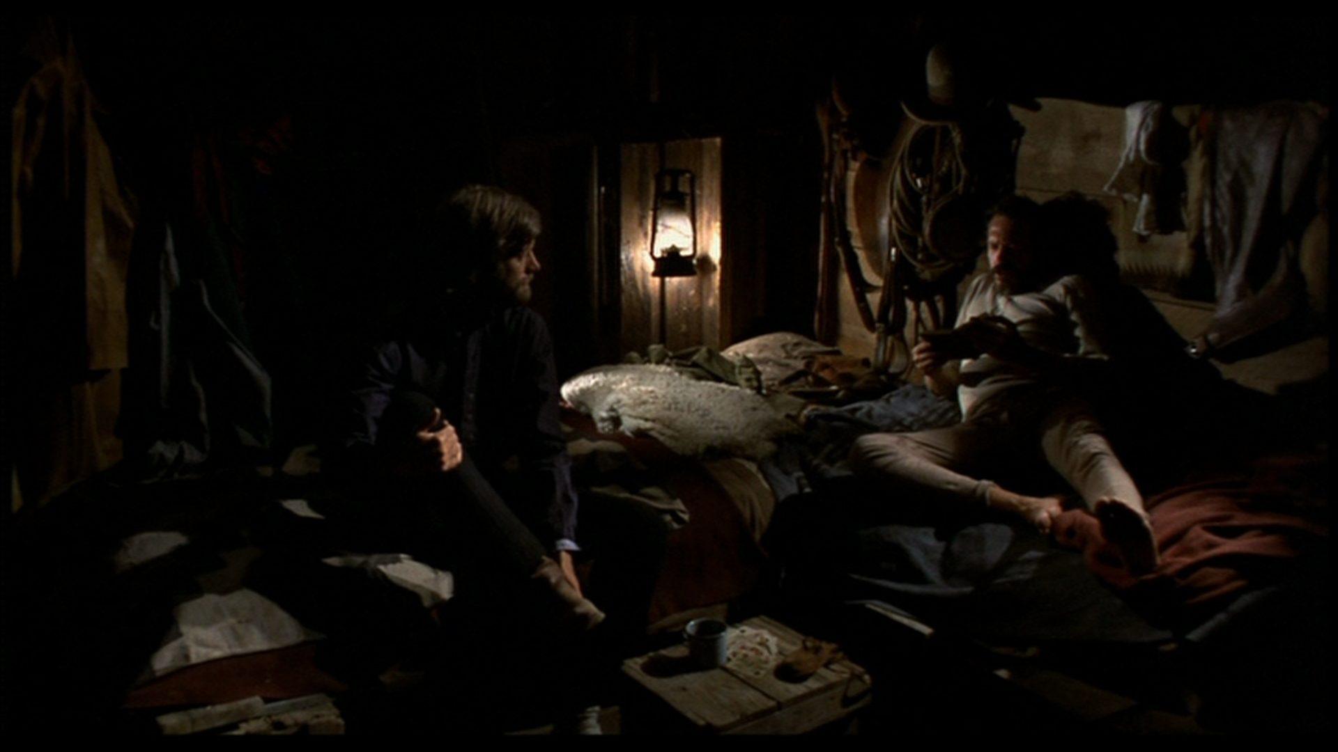 Harry Collings und Arch Harris gehen in einer spärlich erleuchteten Hütte zu Bett.