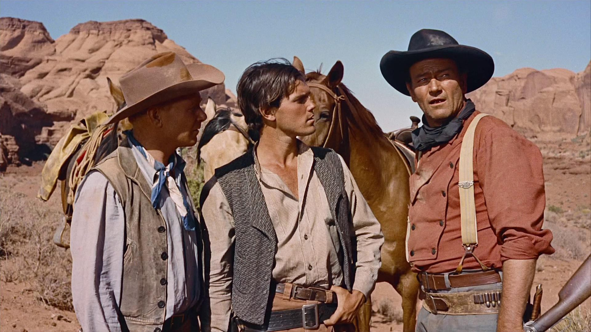 John Wayne als Ethan Edwards mit zwei Kompagnons bei warmem Klima in der Wüste.