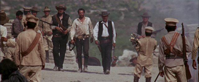 Die Banditen marschieren bewaffnet durch einen mexikanischen Ort.