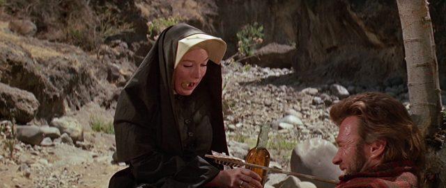 Schwester Sara hat einen Korken zwischen den Lippen und reicht dem von einem Pfeil verwundeten Hogan eine Flasche Whiskey.