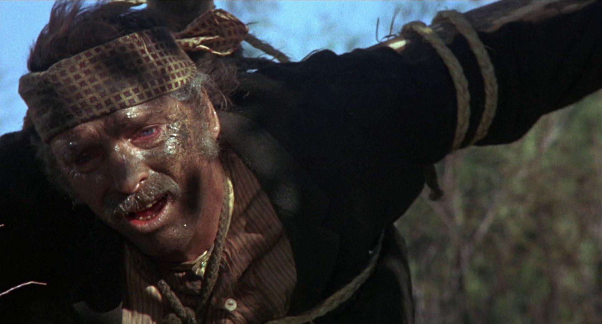 Nahaufnahme von Burt Lancaster als Valdez, der mit strapaziös-ramponiertem Gesicht an ein Holzkreuz gefesselt durch die Wildnis torkelt.