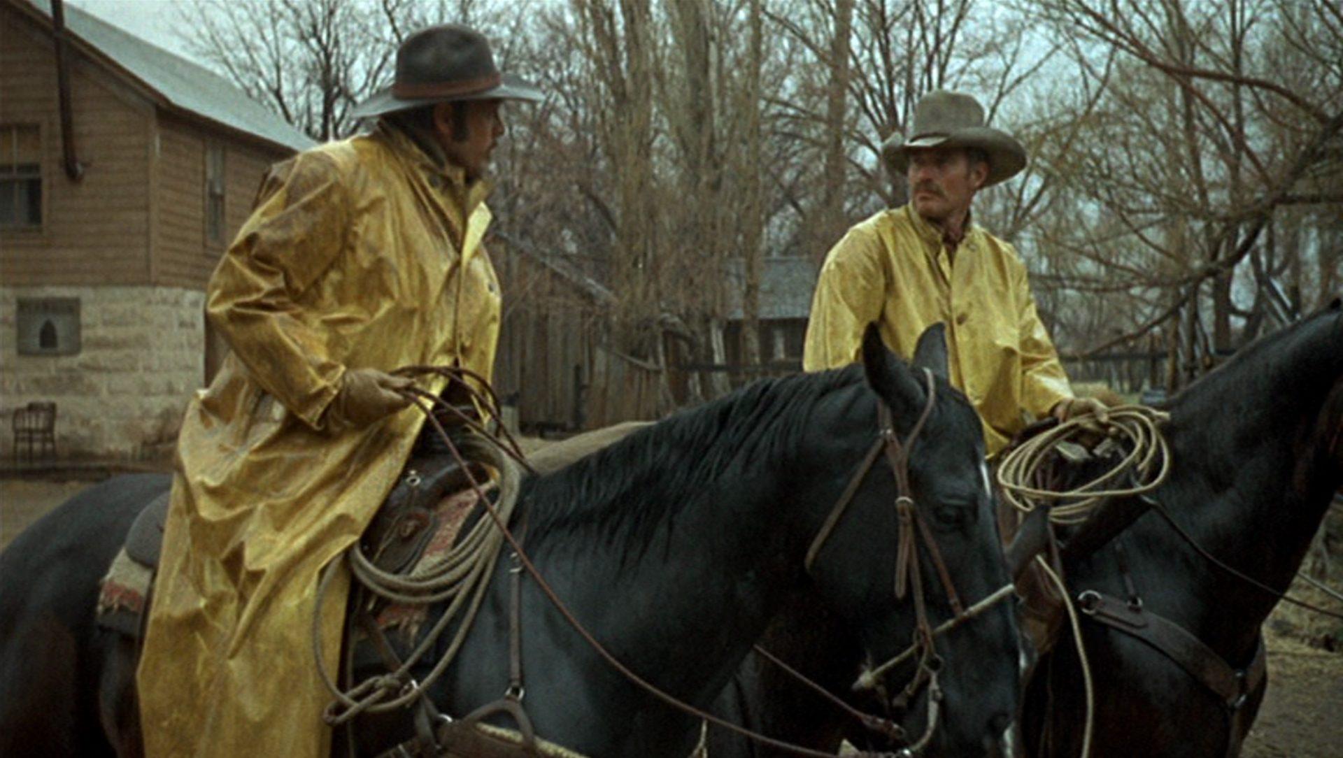 Will Penny im Gespräch mit einem Rancharbeiter zu Pferd in Regenjacken.