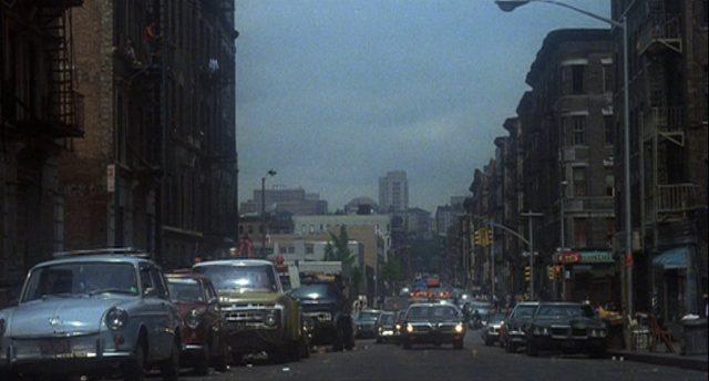 Blick durch eine innerstädtische Straße, auf der sich Fahrzeuge nähern.