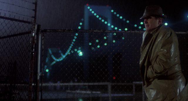 Robert Duvalls Protagonist im Regen vor einem Maschendrahtzaun, im Hintergrund eine der großen New Yorker Brücken.