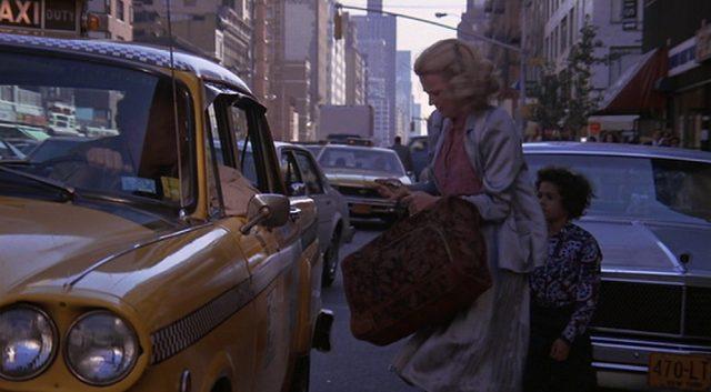 Gloria und Phil an einem Taxi am Rand einer dicht befahrenen Straße.
