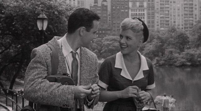 Jack Lemmon und Judy Holliday, deren Charaktere sich angeregt beim Spaziergang durch den Central Park unterhalten; im Hintergrund ein See und Hochhäuser.