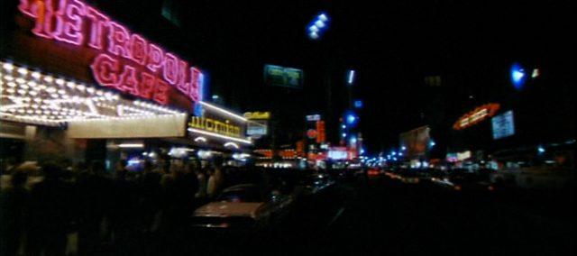 Blick durch eine nachts viel Neonreklame erleuchtete Straße.