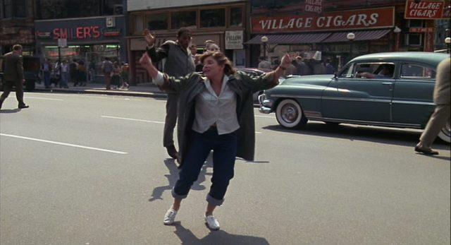Eine Gruppe junger Bohemians tanzt über eine Straße.