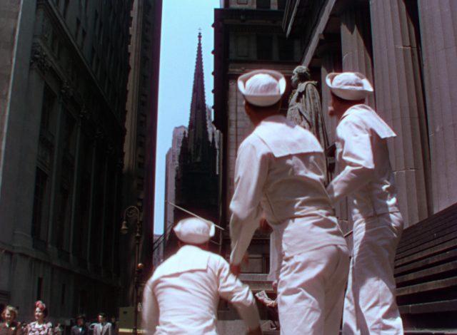 Die drei Matrosen blicken mit dem Rücken zur Kamera durch eine New Yorker Straßenschlucht.