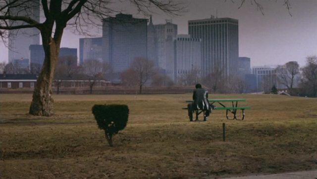 Distanzierter Blick auf Daniel Ciello, der in herbstlicher Umgebung mit dem Rücken zur Kamera und gesenktem Kopf auf einer Parkbank vor einer großstädtischen Hochhauskulisse sitzt.