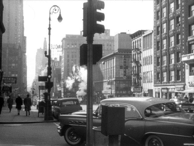 Großstädtische Straßenecke, an der gerade eine Limousine abbiegt, im Hintergrund Hochhäuser.