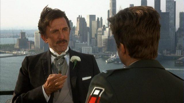 Kirk Douglas als Gangsterboss im Gespräch mit seinem Bruder auf einem Gebäudedach mit der Skyline von Manhattan im Hintergrund.