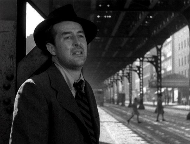 Nahaufnahme von Ray Milland als Alkoholiker mit verzwewifeltem Gesicht unter einer Hochbahnstrecke.
