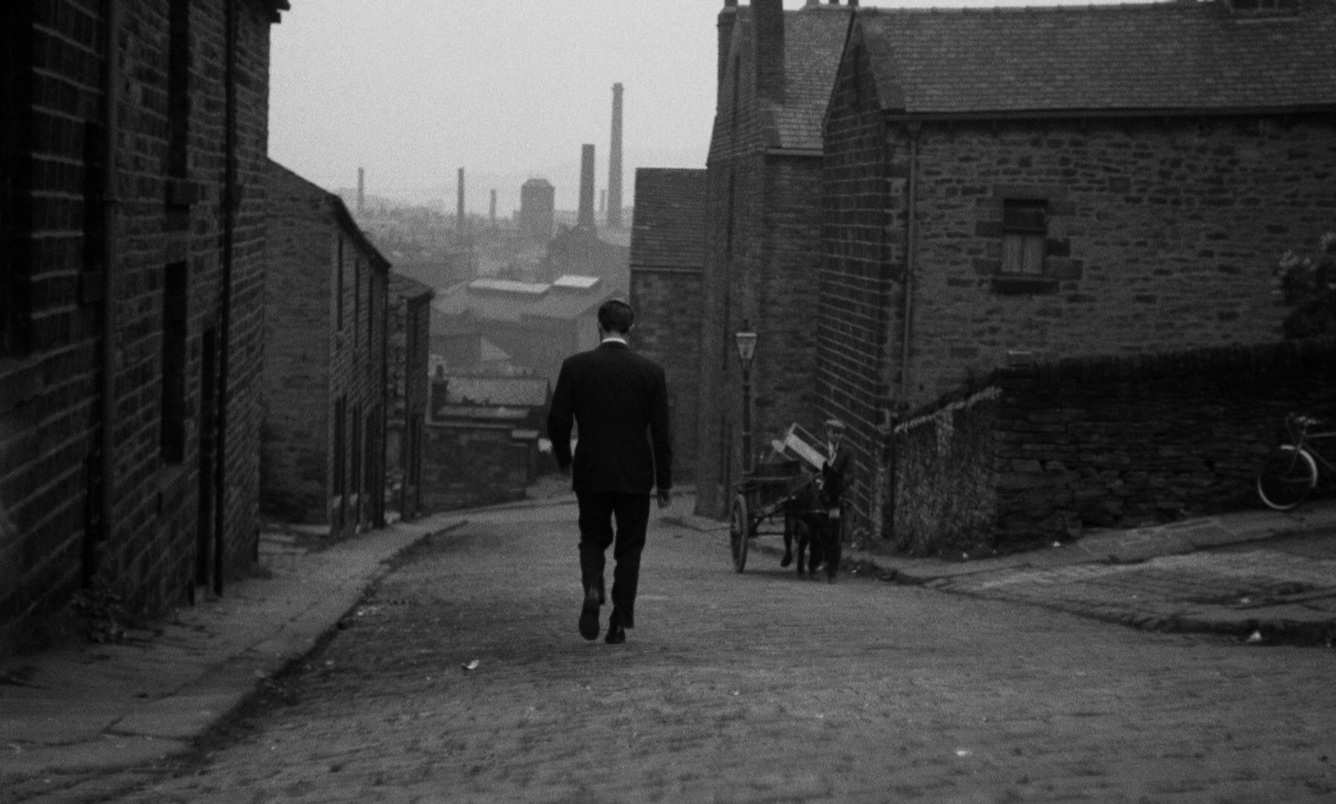 Blick eine Straße eines Arbeiterviertels hinunter, auf den Rücken eines hinuntergehenden Mannes; am Straßenrand geht ein Mann mit seinem Wagen, den ein Esel hinaufzieht; im Hintergrund ragen Fabrikschlote empor.