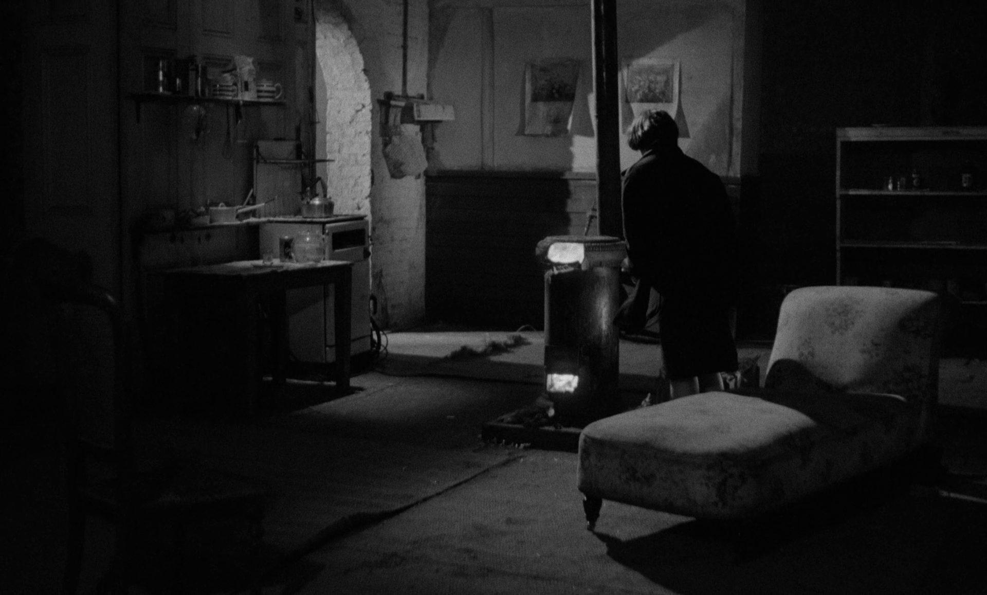 Blick in eine dunkle, karge Mietwohnung, in deren Mitte ein entflammter Ofen steht.