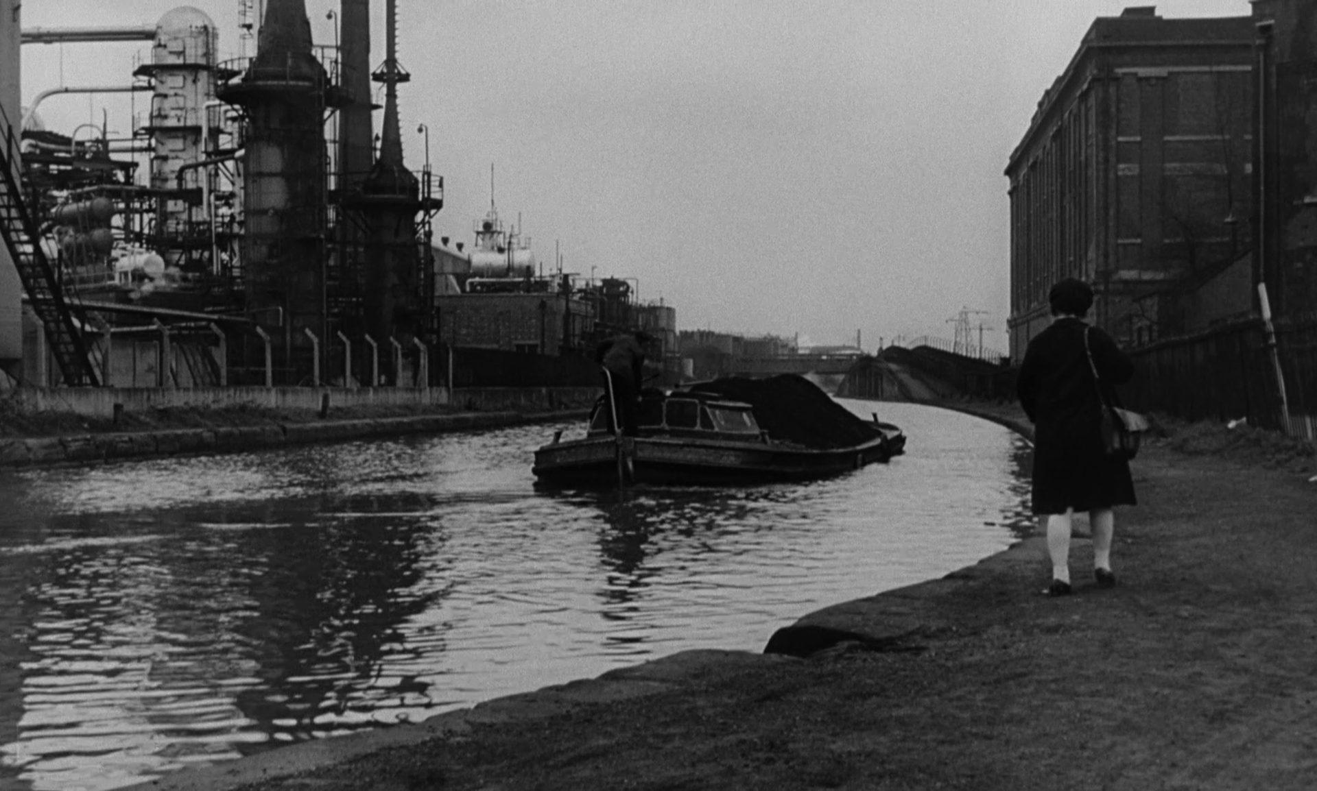 Ein kleines Binnenschiff auf einem Fluss, im Hintergrund eine Industrieanlage, am Ufer geht Jo entlang.