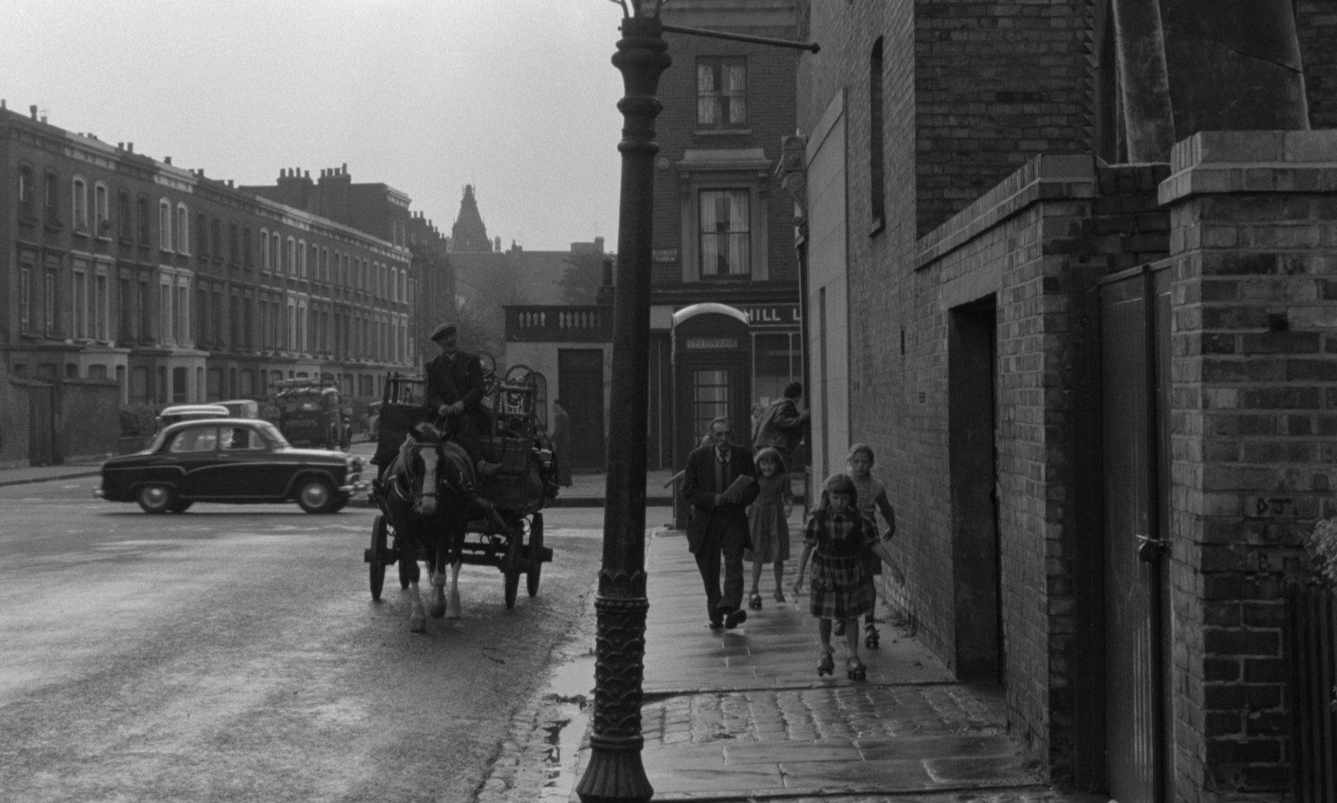Blick in eine Straße, auf der neben einem Auto auch ein Pferdewagen unterwegs ist.
