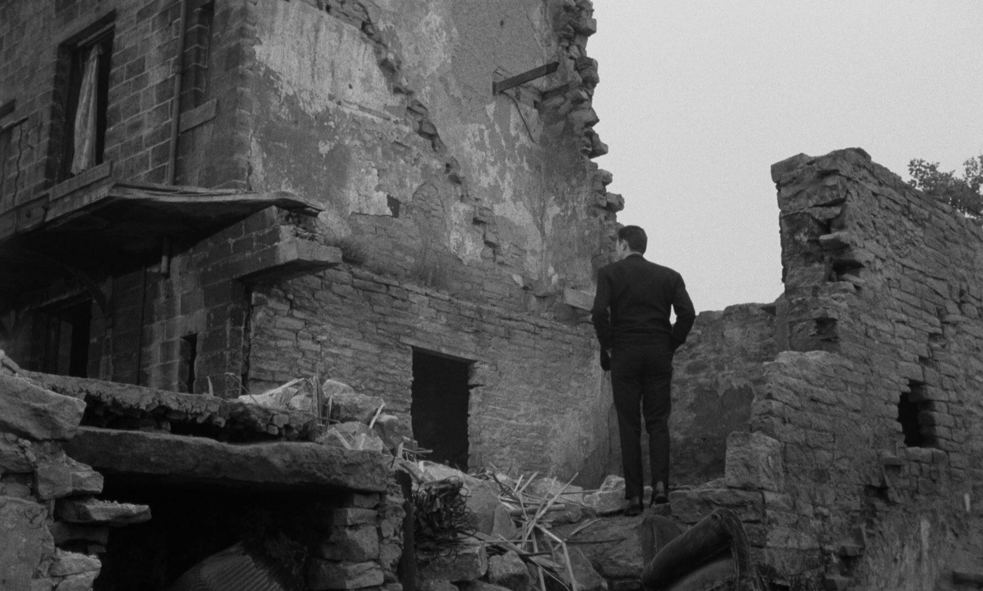 Laurence Harvey als Joe Lampton vor einer Kriegsruine.