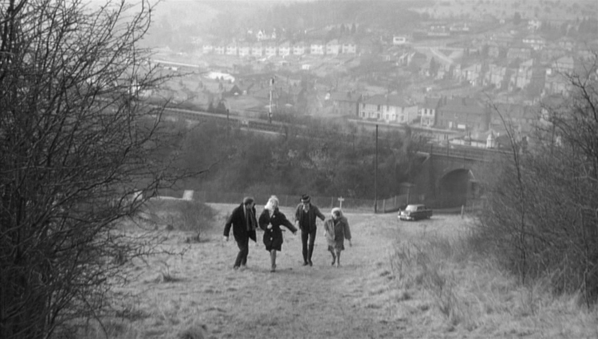 Zwei Paare aus je einem jungen Mann und einer jnungen Frau gehen einen am Stadtrand gelegenen Hügel hinauf, im Hintergrund ist ein Arbeiterquartier zu erkennen.