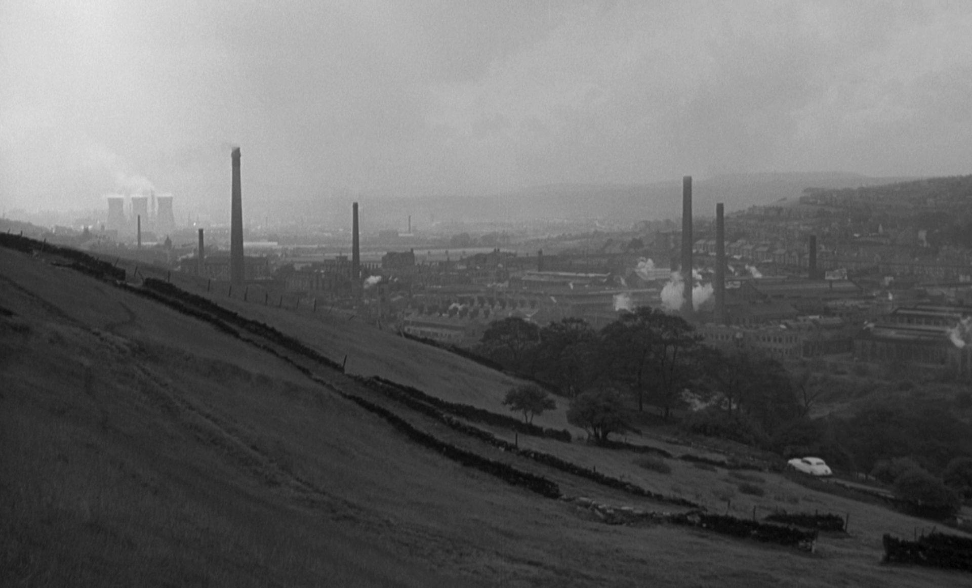 Blick von einem Hang am Stadtrand aus auf eine Industriestadt, aus der einige Fabrikschornsteine herausragen.