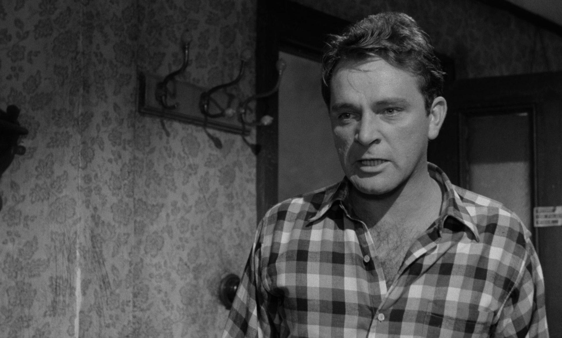 Nahaufnahme von Richard Burton als Jimmy Porter mit zornigem Gesichtsausdruck, gekleidet im Holzfällerhemd, in seinem kargen Appartement.