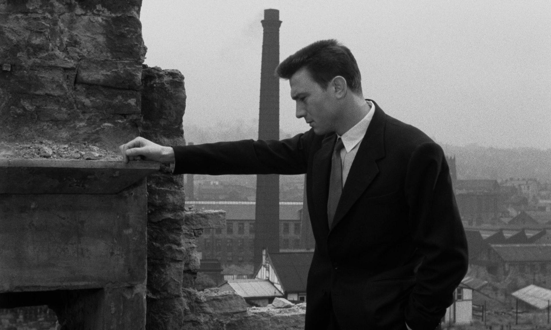 Laurence Harvey als Joe Lampton, der vor industriellem Hintergrund mit ausgestrecktem Arm in bedächtiger Pose an einer Backsteinruine lehnt.