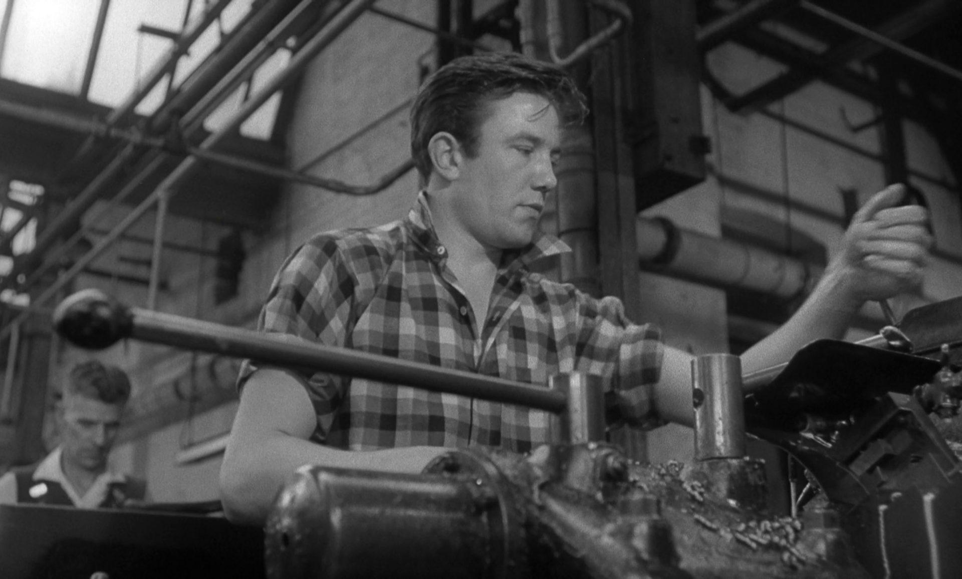 Nahaufnahme von Albert Finney als Arthur Seaton an seinem Fabrikarbeitsplatz im karierten Hemd mit hochgekrempelten Ärmeln.